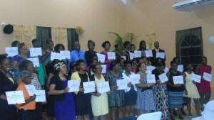 Graduating class with tutor Sylvester Wallace at back in blue shirt