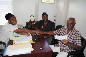 Mr Fredrick Robins-Doras receives his cheque from SWRF Officer Ms Diana Duncan. Looking on is SWRF Officer Thyra Gumbs.