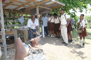 Students of the Gingerland Secondary School looking on as a blacksmith demonstrates how iron objects were made in Nevis yesteryear, at the Ministry of Tourism's Nevisian Heritage Life at the Nevisian Heritage Village in Zion on May 05, 2016