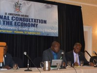 PM Harris (left), next to Premier Vance Amory at the headtable, looks at stakeholders attending the National Consultation on the Economy.