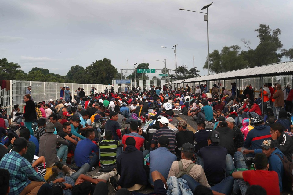 20 October 2018: Participants in the migrant caravan sit on a bridge over the Suchiate River which forms the Guatemala-Mexico border in Ciudad Tecun Uman, Guatemala. (Photograph by John Moore/Getty Images)