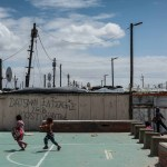 24 September 2018: Children play in front of recently- scrawled gang tags in Blikkiesdorp.