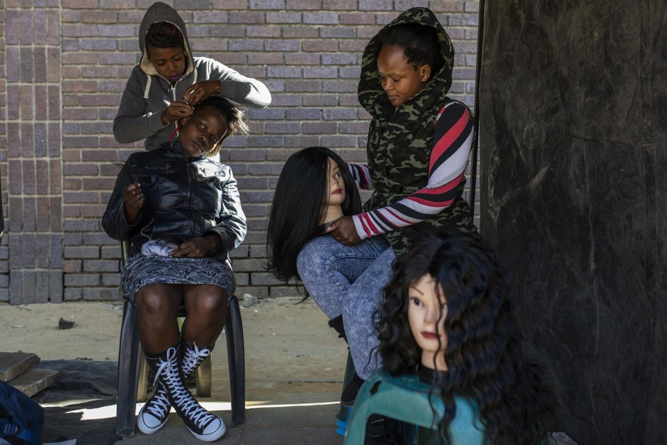 Anita Antonio (right) from Mozambique works as a hairdresser on the sidewalks of Ermelo. She has been operating in the area for around ten years.