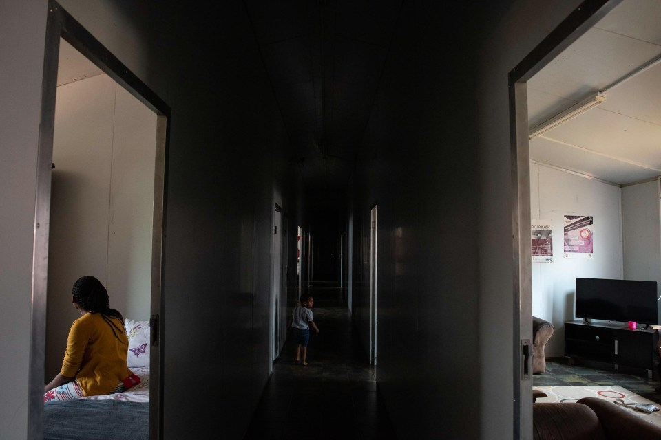 19 September 2018: A woman sits in her room as a child walks down a corridor at A Re Ageng Nthabeleng shelter for victims of domestic violence and sexual assault, in Simunye Township in Randfontein.