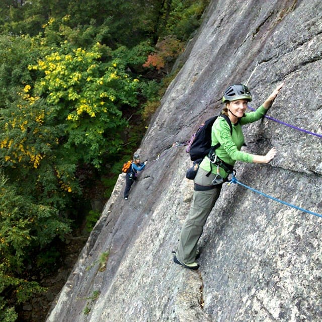 Guided rock climbing the traverse on Thin Air at Cathedral Ledge, New Hampshire.