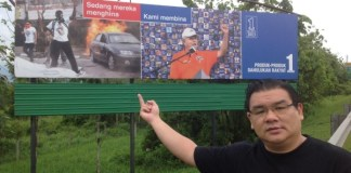 """Superman"" Hew Kuan Yau showing his middle finger at a Barisan Nasional poster."