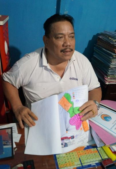 Bapak Darmawan, Nasdem candidate for the local parliament in Kapuas district, Central Kalimantan, with a map outlining his attempts to reach down to voters at the village level. Photo: Edward Aspinall