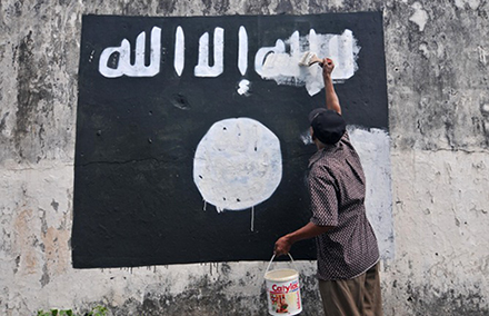 A city worker paints over an IS flag on a wall in Surakarta, Indonesia. Photo by AAP.