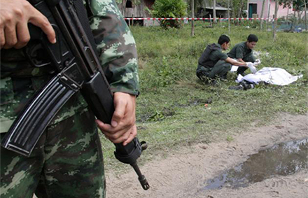 Soldiers inspect the body of a suspected insurgent after a clash with Marines at a navy base in Narathiwat province, southern Thailand. Photo: The Nation.