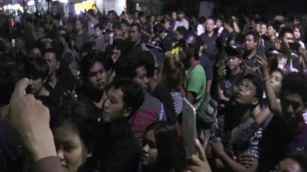 A mob gathers outside Mr Suthee's shop in Phuket.