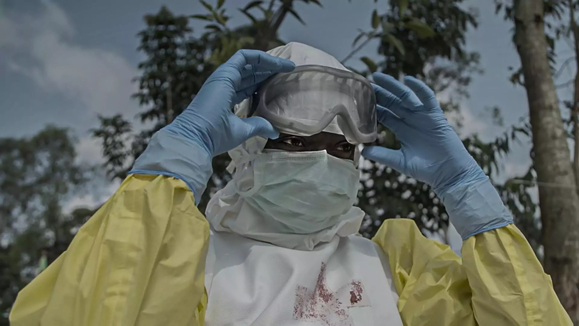 A medical worker peels off their goggles and looks off-screen.