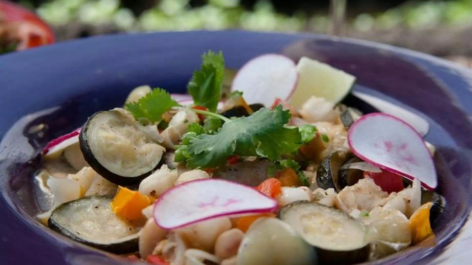 Close-up of a dish including mint, radishes, pasta, and more.