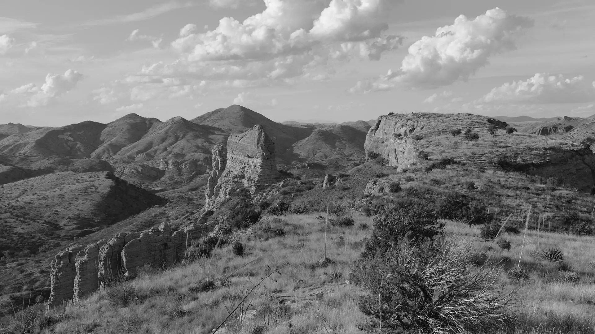 Black-and-white view of a rocky desert range.