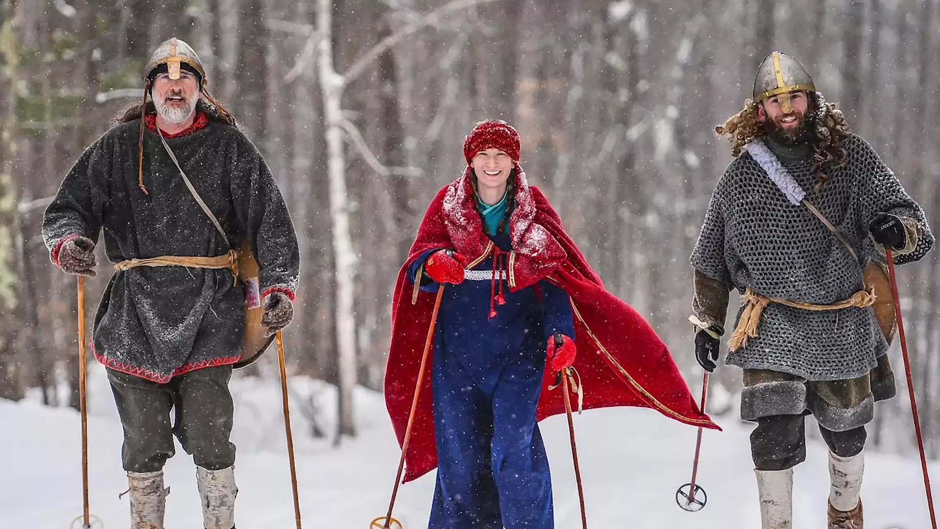 Three people in Nordic dress walk through a snowy forest.