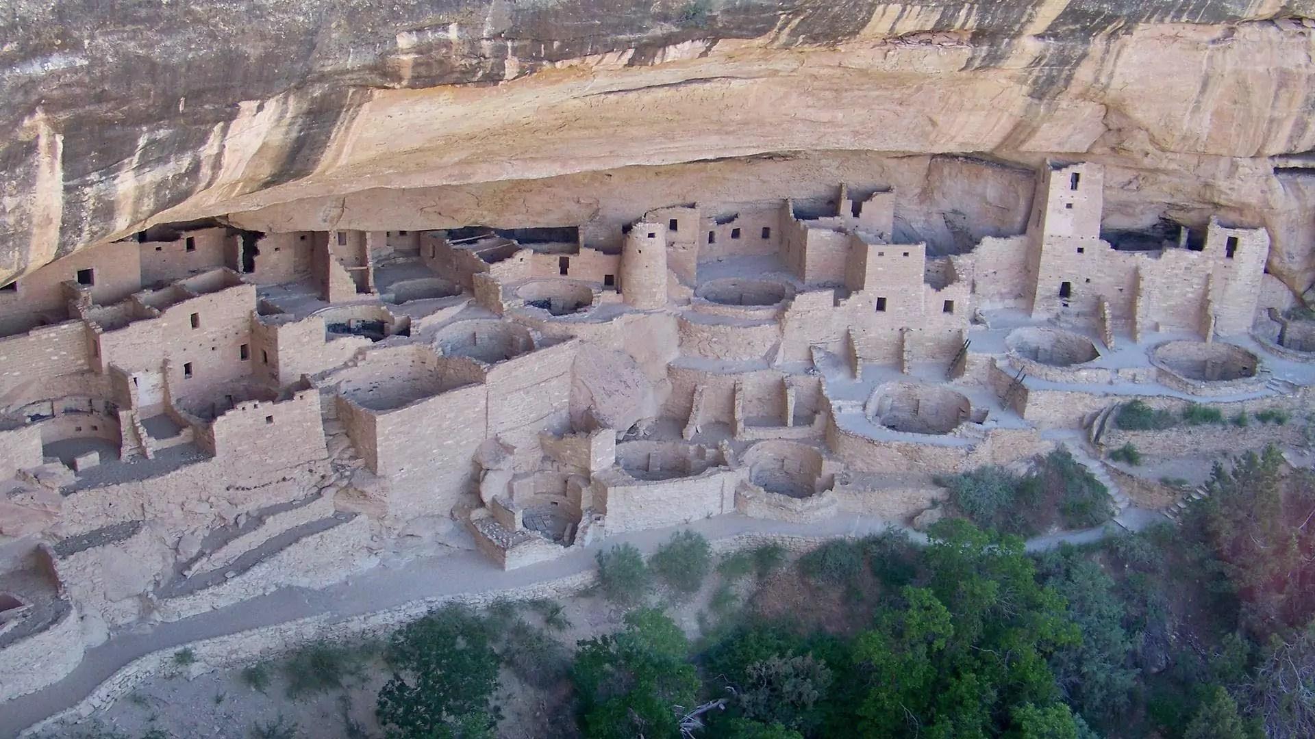Structures of a Pueblo village next to a cliff.
