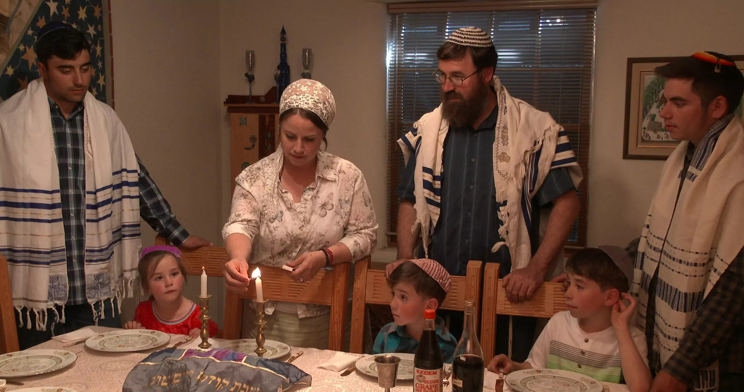 A Jewish family stands around a table.