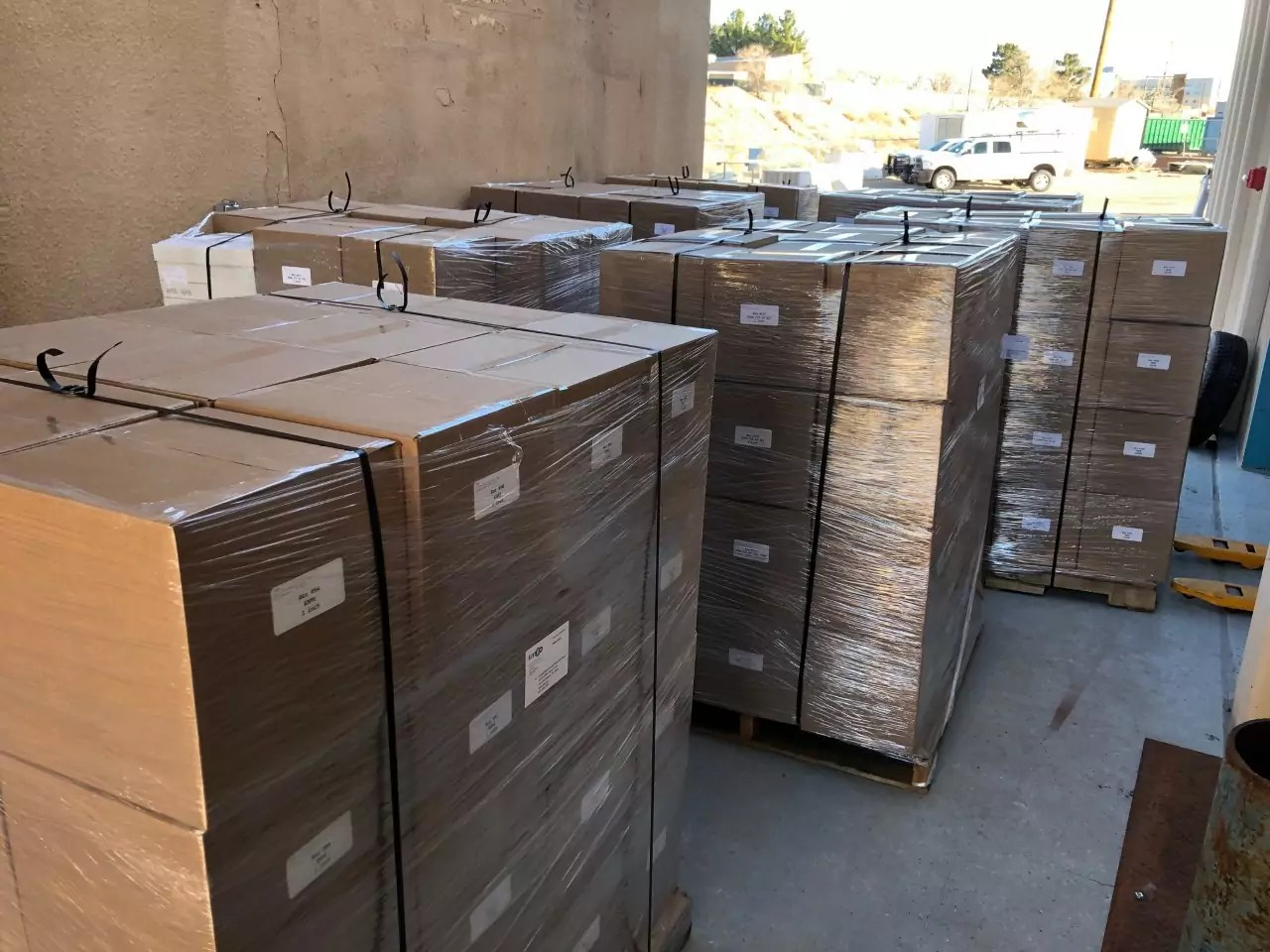 Pallets carrying shrink-wrapped boxes stand ready for processing.