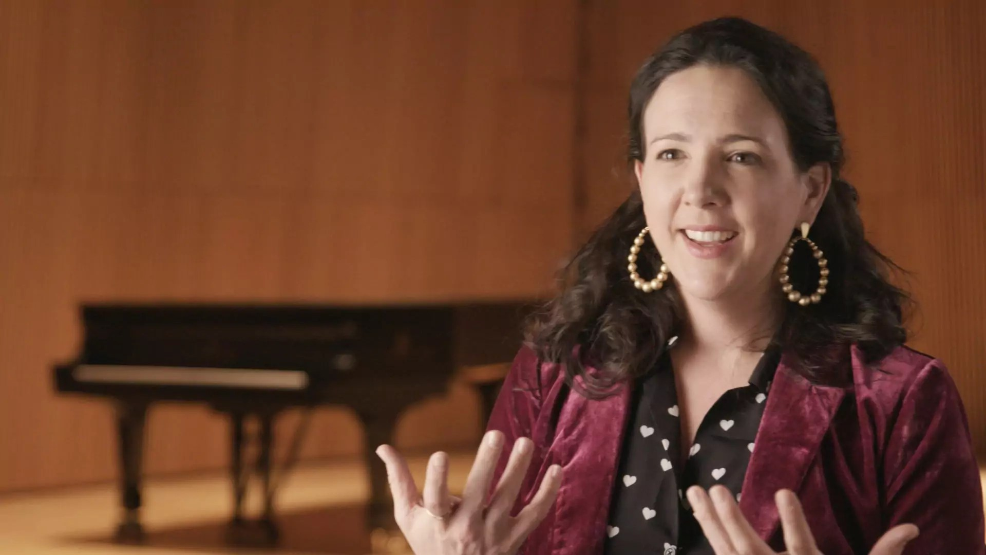 A woman sitting in front of an piano during an interview