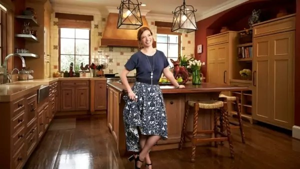 A person in a dress standing in a beautiful kitchen.