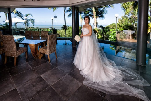 Full length formal portrait of bride inside with amazing view outside through windows. Wedding photography at Palm Cove by Excitations