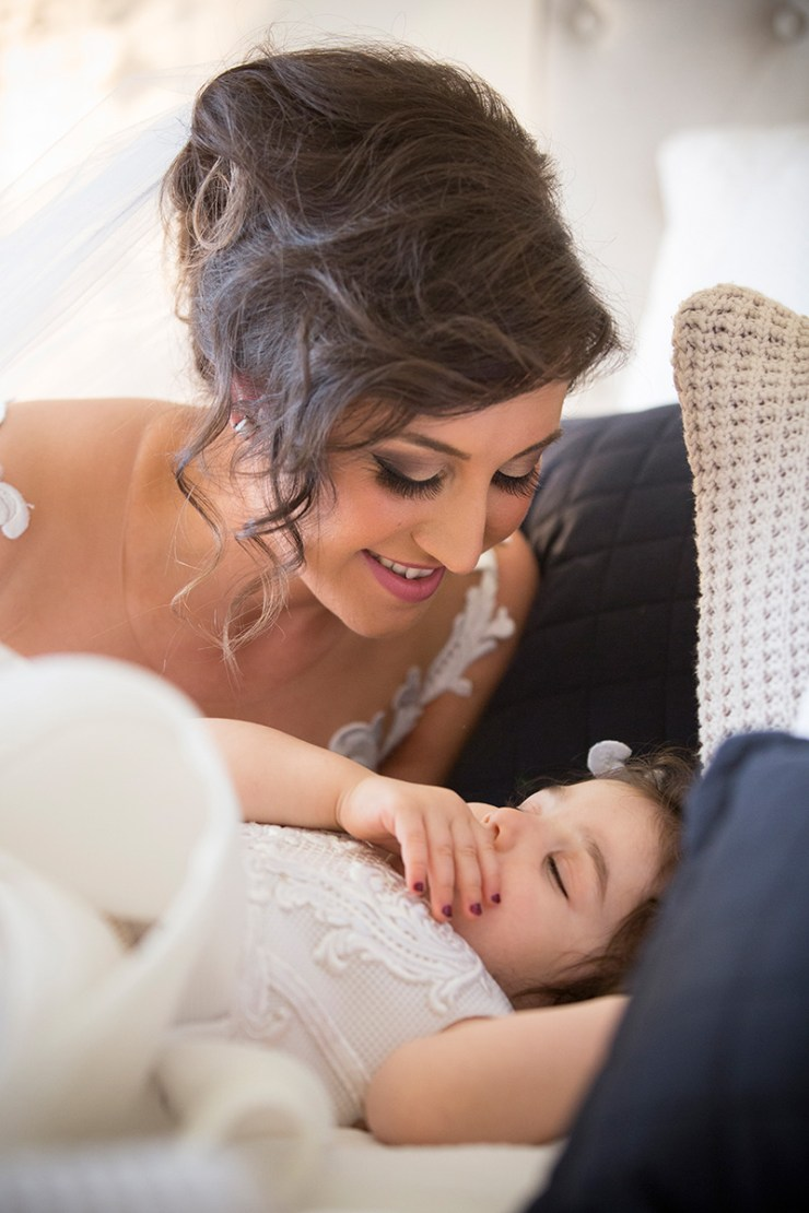 Close up of bride with sleeping flower girl prior to wedding in Mildura.