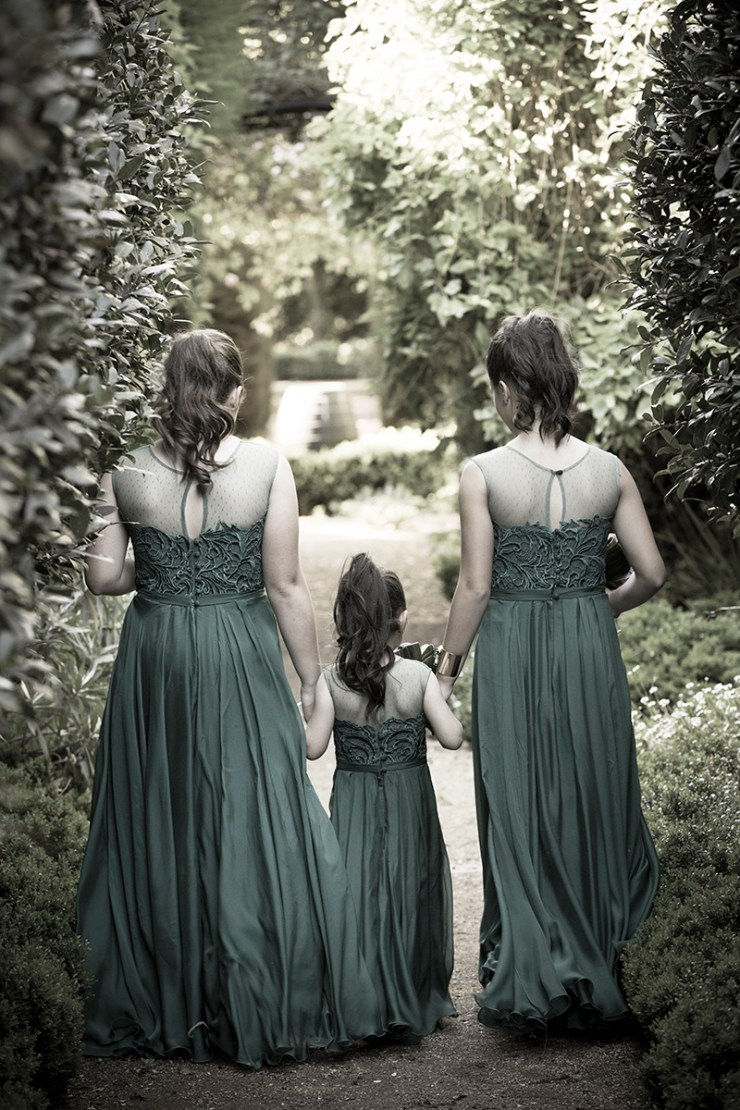 Back view , half toned photograph of three bridesmaids walking through Ampelon Gardens near Mildura. Wedding photos in Mildura by Excitations.