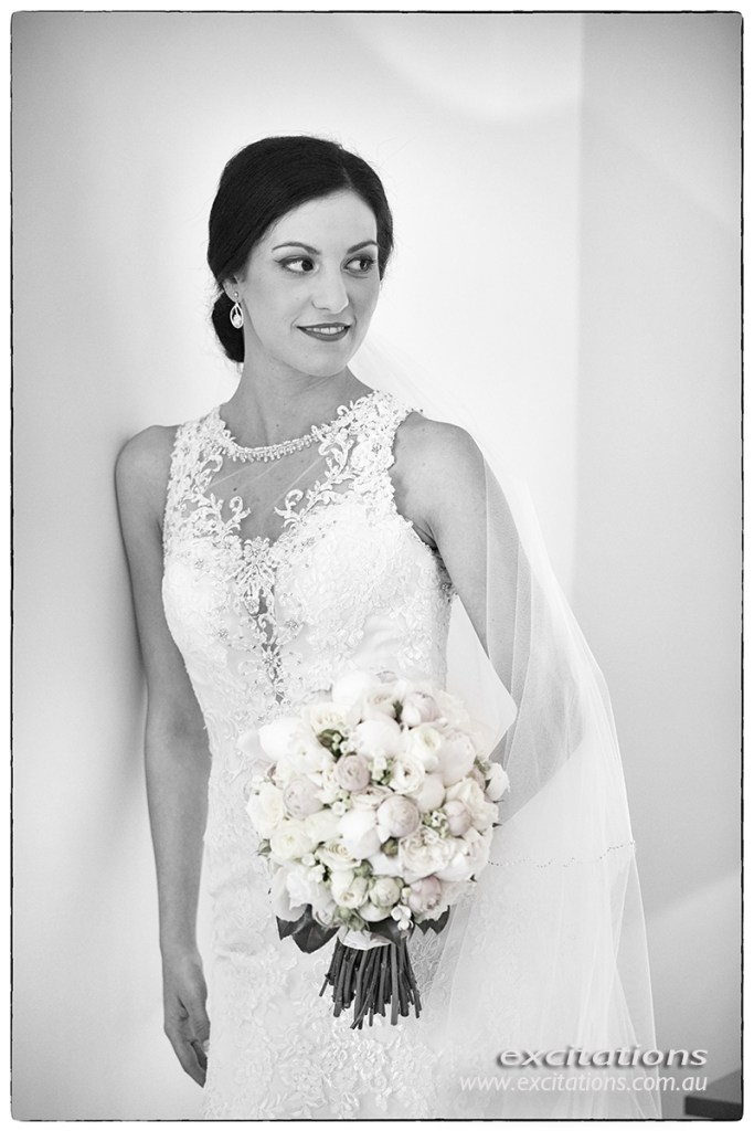 Black and white, half length image of bride leaning against white wall. Photo by Excitations.