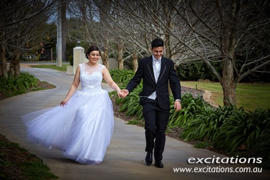 Attractive young Mildura Debutante couple walking down driveway of private residence. Photography by Mildura photography studio, Excitations.