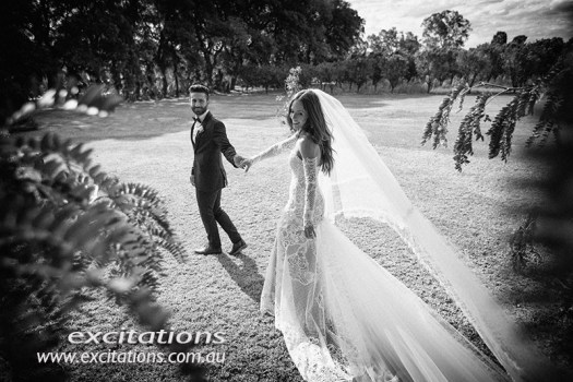 Black and white wedding photo of groom leading bride through an informal garden setting. Photos by Excitations Mildiura photographers.