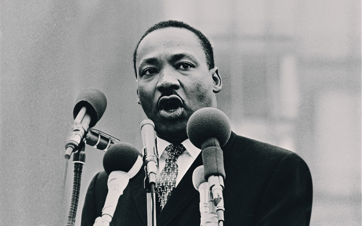Martin Luther King Jr. speaks into several microphones