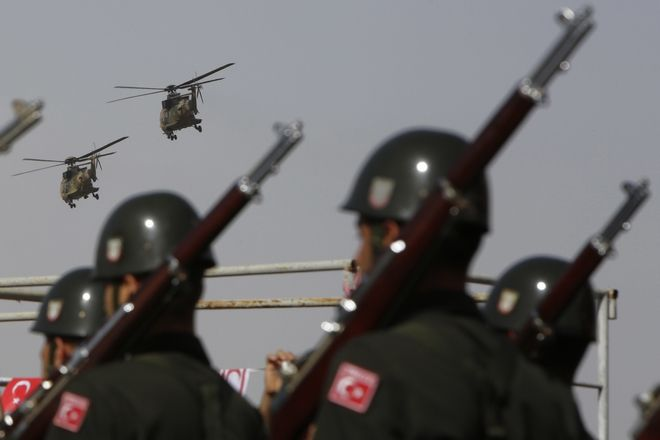 Soldiers march as Turkish air force helicopters fly over a military parade in the Turkish occupied area of the divided capital Nicosia, Cyprus, Wednesday, Nov. 15 , 2017. November 15 marks the 34rd anniversary of the unilateral declaration of independence by the occupation regime, recognized only by Turkey. (AP Photo/Petros Karadjias)