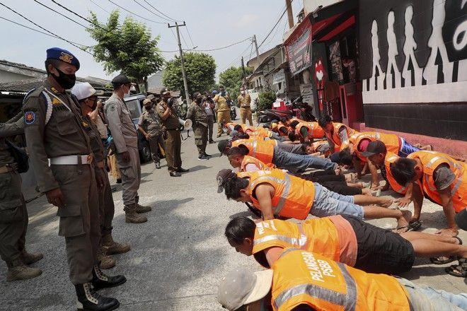 Οι αξιωματικοί της Υπηρεσίας Δημόσιας Τάξης παρακολουθούν τους ανθρώπους να κάνουν push up ως τιμωρία για παραβίαση των κανονισμών της πόλης για χρήση μάσκας σε δημόσιους χώρους, Τζακάρτα, 1 Σεπτεμβρίου 2020.