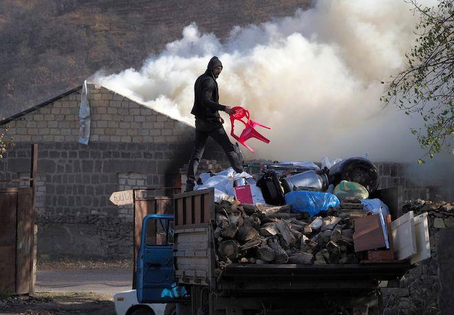 Ένας άντρας φορτώνει αντικείμενα στο φορτηγό του αφού έβαλε φωτιά στο σπίτι του, σε μια περιοχή που σύντομα θα παραδοθεί στο Αζερμπαϊτζάν, Παρασκευή 13 Νοεμβρίου, 2020.