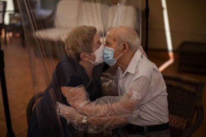 Ηλικιωμένο ζευγάρι ανταλλάζει φιλί ενώ ανάμεσά τους υπάρχει πλαστικό, Ισπανία