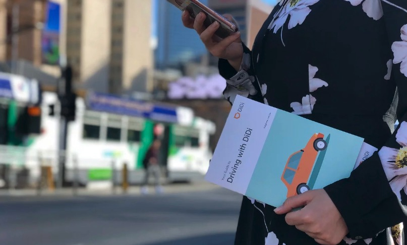 "A woman holds a ""Driving with Didi"" pamphlet. /Photo courtesy of Technode"
