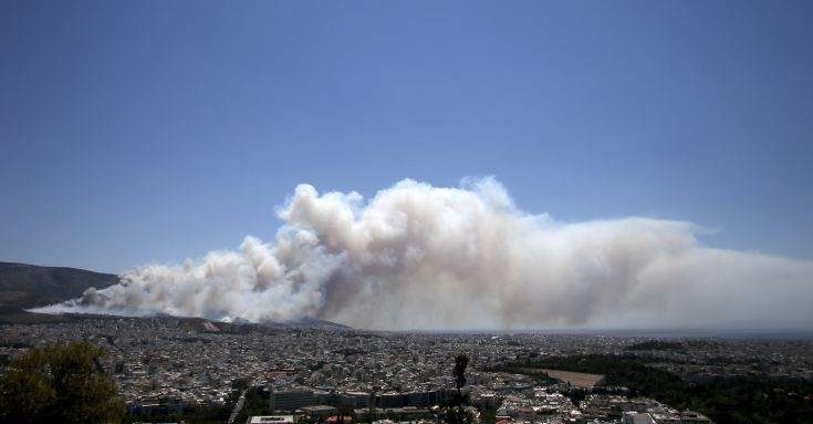 Smoke rises as a wildfire rages at the Kareas suburb, east of Athens, Greece July 17, 2015. Dozens of Athens residents fled their homes on Friday as wildfires fanned by strong winds and high temperatures burned through woodland around the Greek capital, sending clouds of smoke billowing over the city.    REUTERS/Alkis Konstantinidis