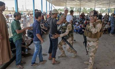 Iraqi soldier inspects a displaced Iraqi members at a temporary camp