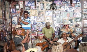 Musicians playing their instruments in front of a wall covered with photos at Casa de la Trova, Santiago de Cuba, Cuba.