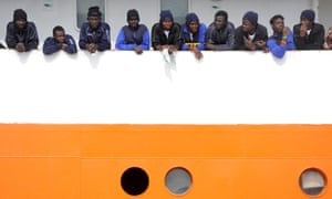 Migrants wait to disembark from Aquarius in the Sicilian harbour of Catania, Italy, May 2018.