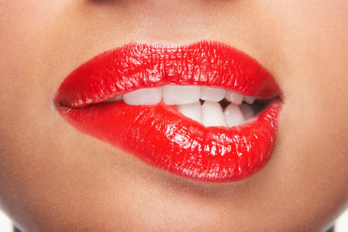 Woman wearing red lipstick biting her lip
