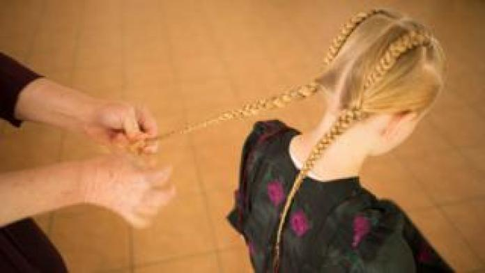 Mennonite girl has her hair plaited