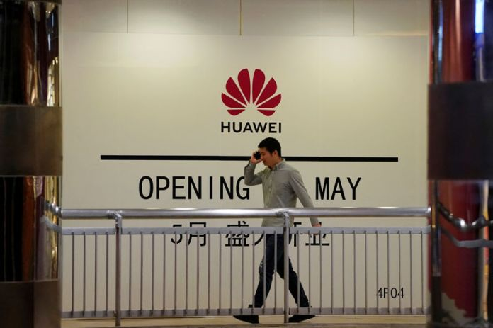 © Reuters. Man using his mobile phone walks past a yet-to-open Huawei store inside a shopping mall in Shanghai