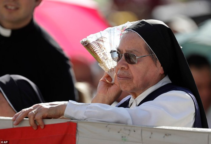 A nun uses a fan to shelter from the sun as she waits for the start of Pope Francis' general audience in St. Peter's Square