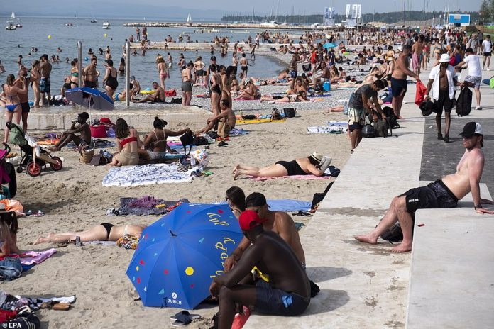 People enjoy the sunny and warm weather on the beach plage des Eaux-Vives on the shore of Lake of Geneva, in Geneva, Switzerland, Tuesday