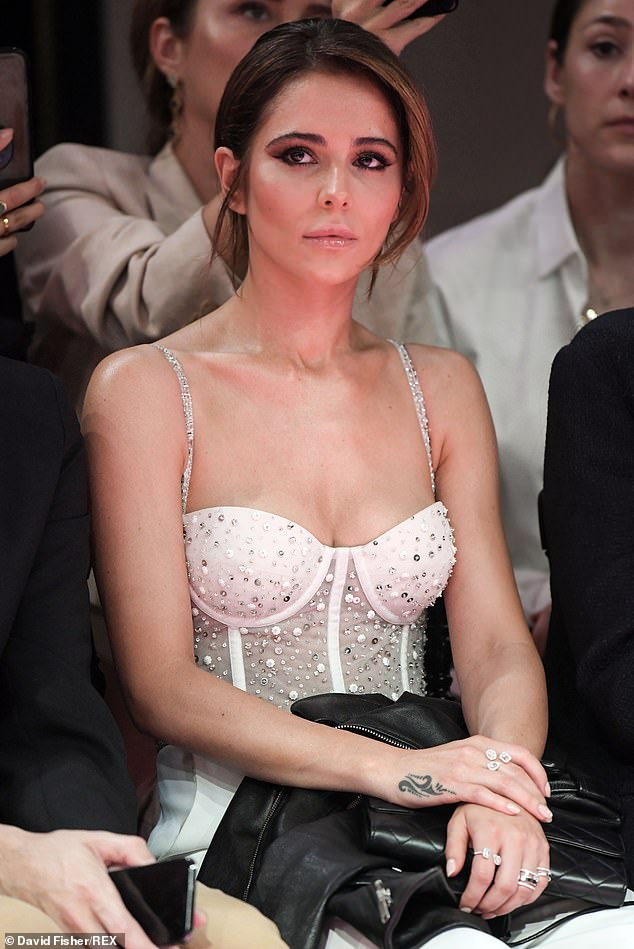 Inspired: Cheryl looked engrossed with the fashion being paraded down the catwalk