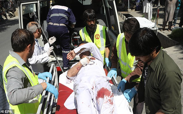 A wounded man - apparently bleeding in his leg - is carried on a stretcher as Afghan rescue workers deal with the aftermath of today's explosion