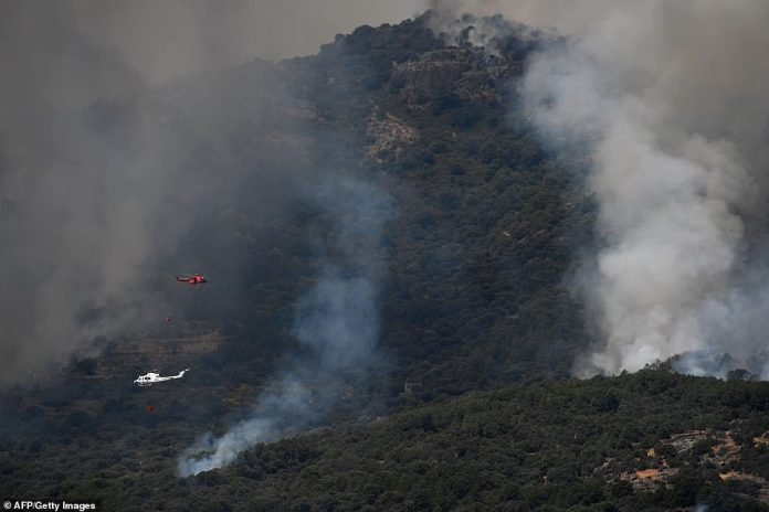 Helicopters drop water over a wildfire in the outskirts of Cadalso de los Vidrios in central Spain on Friday afternoon as authorities battled to contain the fire