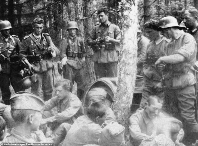 Prisoners: German forces (standing) watch over a group of Russian troops (sitting down), captured at an unknown location on the Eastern Front. The tallest of the Germans is unfolding a camera. Any 'political commissars' among the Russian forces faced execution under an order issued by the Nazi high command in 1941, shortly before the invasion of the USSR began. Many Russian prisoners were taken to concentration camps or died during death marches