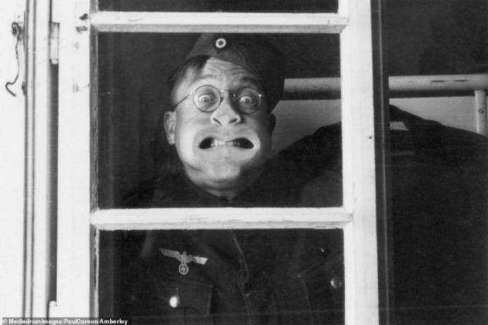 Making faces: This German soldier is making a daft face as he poses for a picture, seemingly through a window. Many German soldiers brought their own cameras with them when they joined up, creating a huge collection of wartime images - which they would organise in photo albums or have made into postcards