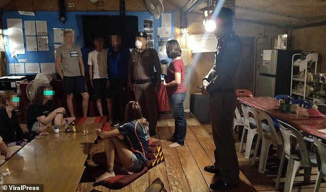A Thai police officer can be seen standing over the group of tourists - which included another two who had not gone swimming